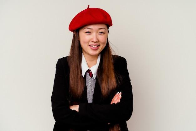 Jeune femme chinoise portant un uniforme scolaire isolé sur un mur blanc en riant et en s'amusant.