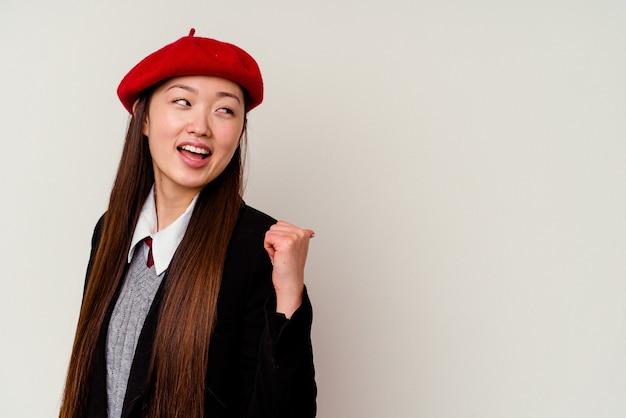 Jeune femme chinoise portant un uniforme scolaire isolé sur des points blancs avec le pouce, riant et insouciant.