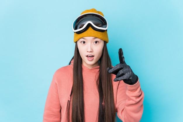 Jeune femme chinoise portant des vêtements de ski isolés ayant une idée, un concept d'inspiration.