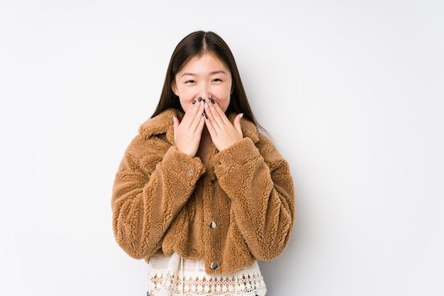 Jeune femme chinoise posant dans un fond blanc isolé en riant de quelque chose, couvrant la bouche avec les mains.