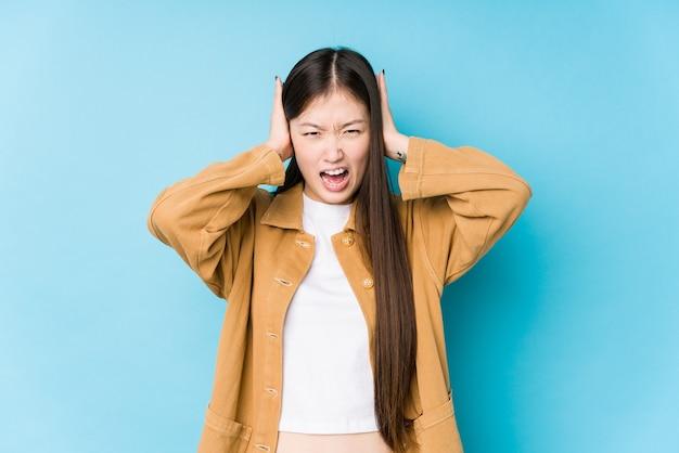 Jeune femme chinoise posant dans un fond bleu isolé couvrant les oreilles avec les mains en essayant de ne pas entendre un son trop fort.