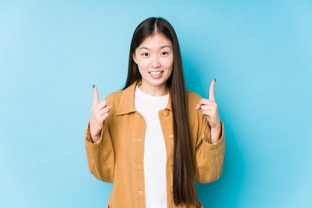 Jeune femme chinoise posant dans un fond bleu isolé indique avec les deux doigts avant montrant un espace vide.