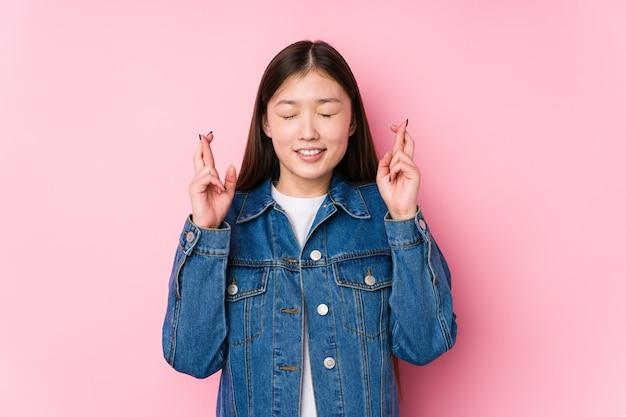 Jeune femme chinoise posant dans un fond rose isolé doigts croisés pour avoir de la chance