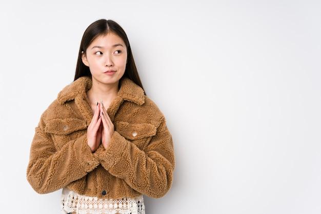 Jeune femme chinoise posant dans un mur blanc isolé, plan de préparation à l'esprit, mise en place d'une idée.