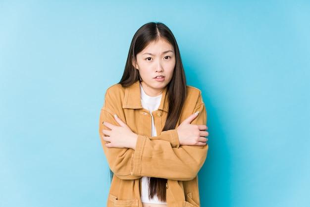 Jeune femme chinoise posant dans un mur bleu isolé qui devient froid en raison d'une basse température ou d'une maladie.
