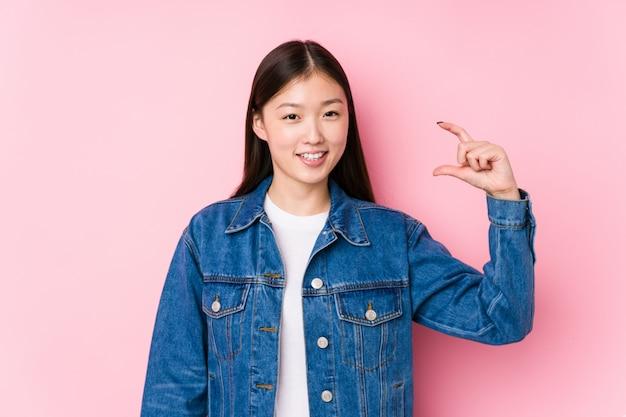 Jeune femme chinoise posant dans un mur rose isolé tenant quelque chose de peu avec les index, souriant et confiant.