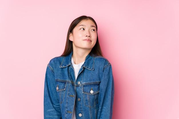 Jeune femme chinoise posant dans un mur rose rêvant d'atteindre ses objectifs