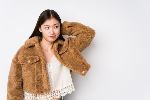 Jeune femme chinoise posant dans une surface blanche isolée touchant l'arrière de la tête, pensant et faisant un choix.