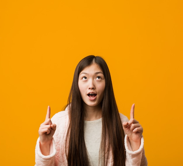 Jeune femme chinoise en pyjama à l'envers avec la bouche ouverte.