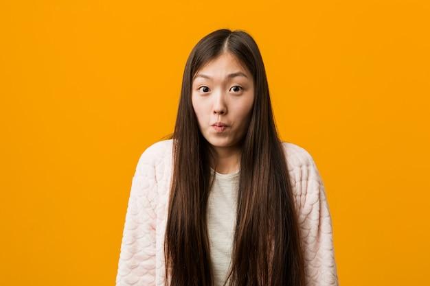 Une jeune femme chinoise en pyjama hausse les épaules et ouvre grand les yeux confus.