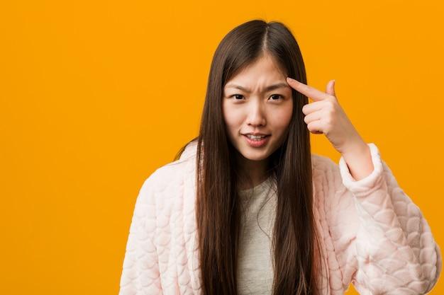 Jeune femme chinoise en pyjama montrant un geste de déception avec l'index.