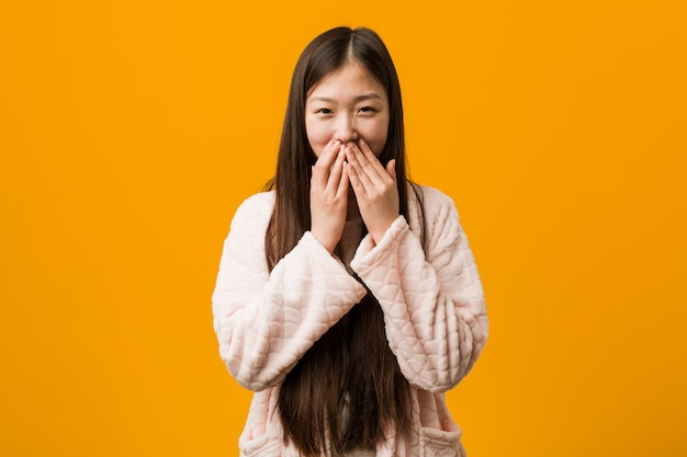 Jeune femme chinoise en pyjama rire de quelque chose, se couvrir la bouche avec les mains.