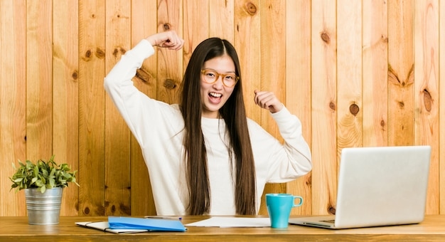 Jeune femme chinoise qui étudie sur son bureau pour célébrer une journée spéciale saute et lève les bras avec énergie.