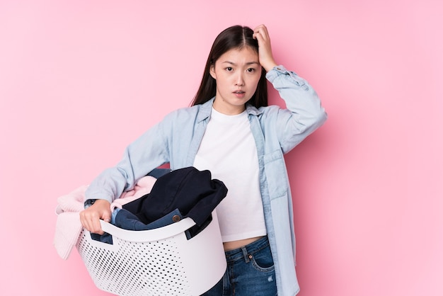 Jeune femme chinoise ramassant des vêtements sales isolés étant choquée, elle s'est souvenue d'une réunion importante.