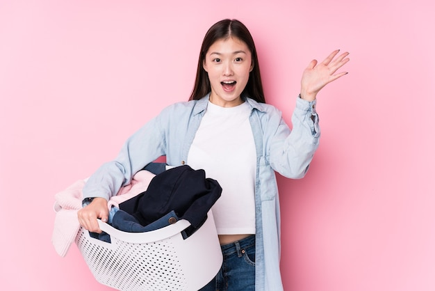 Jeune femme chinoise ramasser des vêtements sales isolés recevant une agréable surprise, excitée et levant les mains.