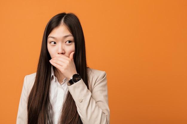 Jeune femme chinoise réfléchie à la recherche d'un espace copie couvrant la bouche avec la main.