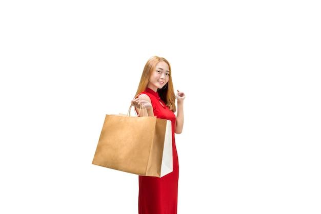 Jeune femme chinoise en robe cheongsam tenant des sacs à provisions