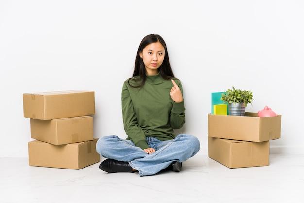Jeune femme chinoise se déplaçant vers une nouvelle maison pointant du doigt vers vous comme si vous vous invitiez à vous rapprocher.