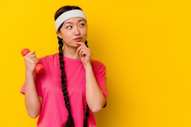 Jeune femme chinoise de sport isolée sur un mur jaune à la recherche de côté avec une expression douteuse et sceptique.