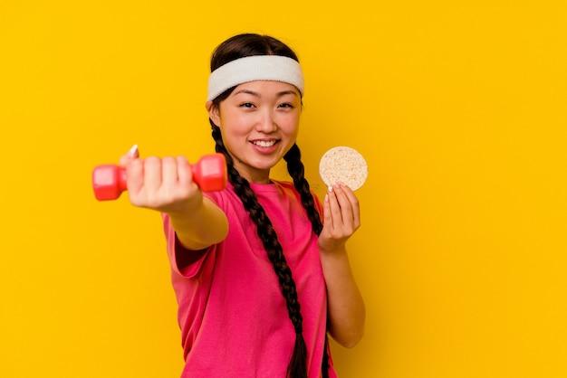 Jeune femme chinoise de sport mangeant des gâteaux de riz isolés sur jaune
