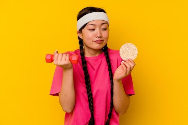 Jeune femme chinoise de sport mangeant des gâteaux de riz isolés sur mur jaune