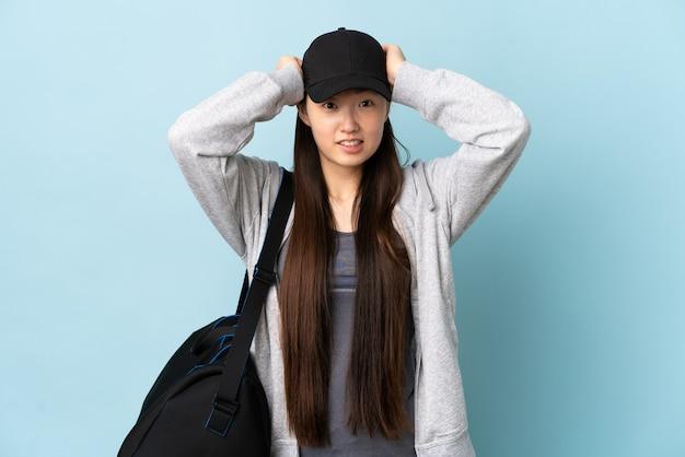 Jeune femme chinoise de sport avec sac de sport sur bleu isolé faisant un geste nerveux