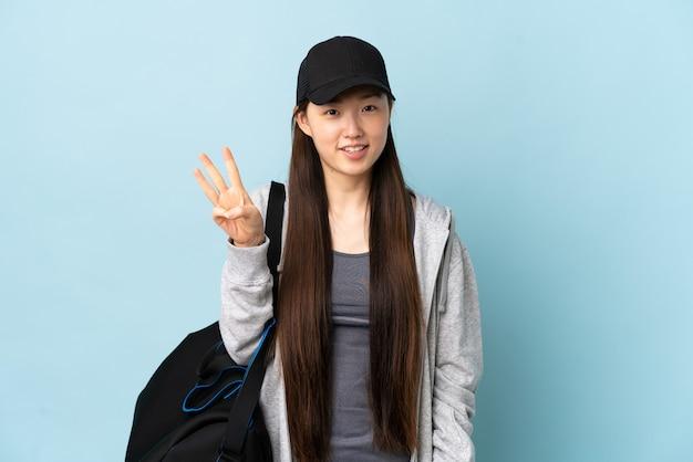 Jeune femme chinoise de sport avec sac de sport sur bleu isolé heureux et comptant trois avec les doigts