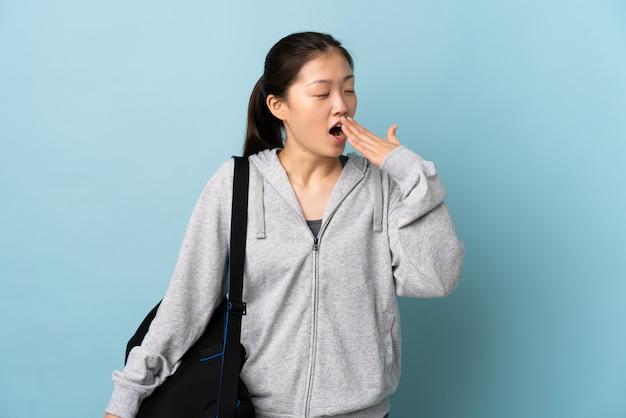 Jeune femme chinoise sport avec sac de sport sur le mur bleu isolé bâillement et couvrant la bouche grande ouverte avec la main
