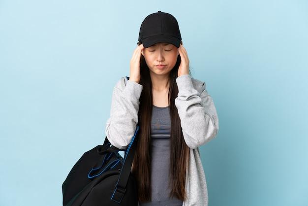 Jeune femme chinoise sport avec sac de sport sur mur bleu isolé avec maux de tête