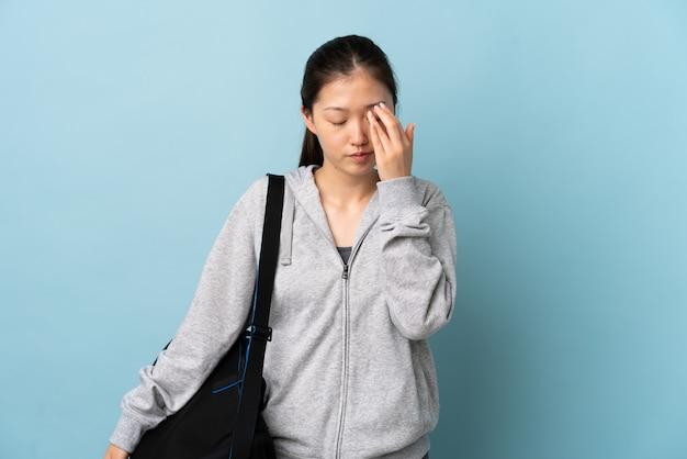 Jeune femme chinoise de sport avec sac de sport sur mur bleu isolé avec maux de tête