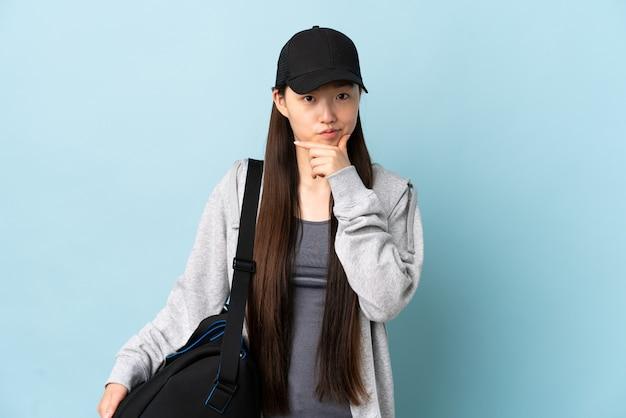 Jeune femme chinoise de sport avec sac de sport sur la pensée bleue isolée