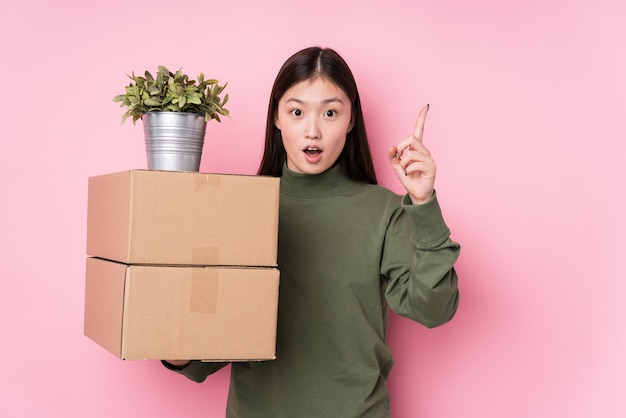 Jeune femme chinoise tenant des boîtes isolées ayant une idée, un concept d'inspiration.