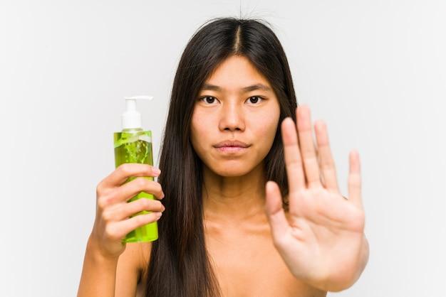 Jeune femme chinoise tenant une crème hydratante à l'aloe vera debout avec la main tendue montrant le panneau d'arrêt, vous empêchant.