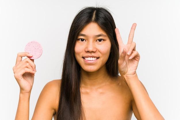 Jeune femme chinoise tenant un disque facial isolé montrant le signe de la victoire et souriant largement.