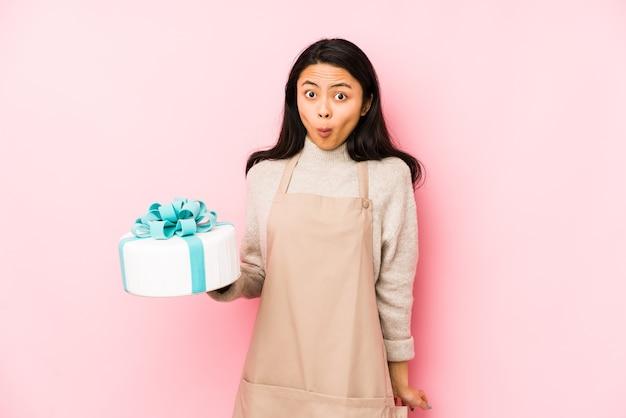 Jeune femme chinoise tenant un gâteau isolé points avec le pouce, riant et insouciant.