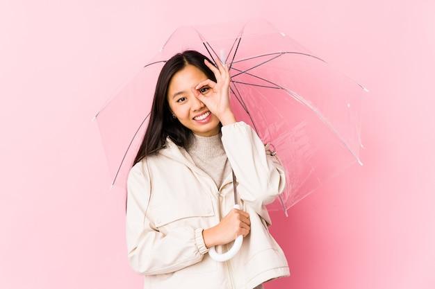Jeune femme chinoise tenant un parapluie isolé excité en gardant le geste ok sur les yeux.