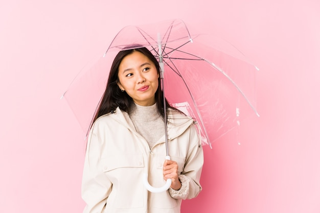 Jeune femme chinoise tenant un parapluie isolé rêvant d'atteindre les objectifs et les buts