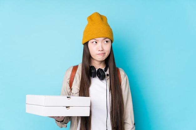 Jeune femme chinoise tenant des pizzas isolés confus, se sent douteux et incertain.