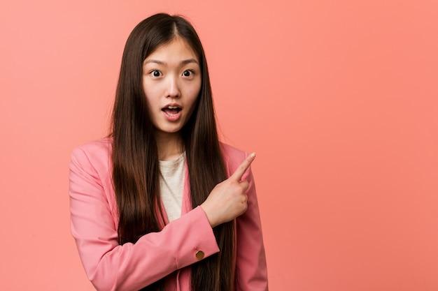 Jeune femme chinoise vêtue d'un costume rose pointant sur le côté