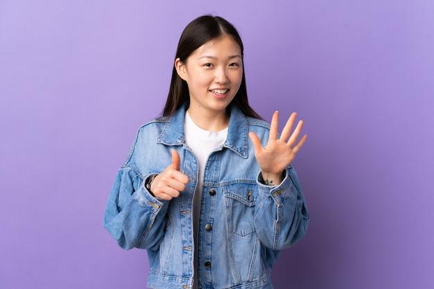 Jeune femme chinoise sur violet isolé comptant six avec les doigts