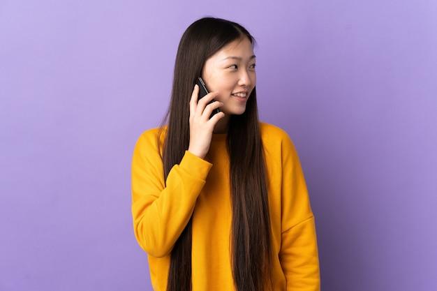 Jeune femme chinoise sur violet isolé en gardant une conversation avec le téléphone mobile avec quelqu'un