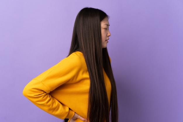 Jeune femme chinoise sur violet isolé souffrant de maux de dos pour avoir fait un effort