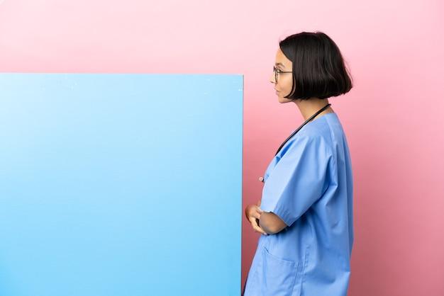 Jeune femme chirurgien métisse avec une grande bannière sur fond isolé en position latérale