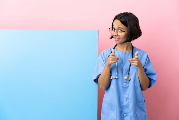 Jeune femme chirurgien métisse avec une grande bannière sur fond isolé surpris et pointant vers l'avant