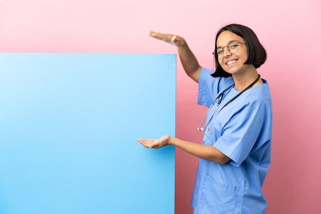 Jeune femme chirurgien métisse avec une grande bannière fond isolé tenant un espace pour insérer une annonce