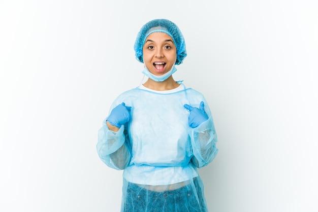 Jeune femme chirurgienne isolée sur un mur blanc surpris en pointant avec le doigt, souriant largement