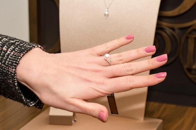 Jeune femme choisissant la bague en bijouterie. main de cliente dans la bijouterie. essayer une bague en diamant avec perle blanche, mode et concept d'achat.