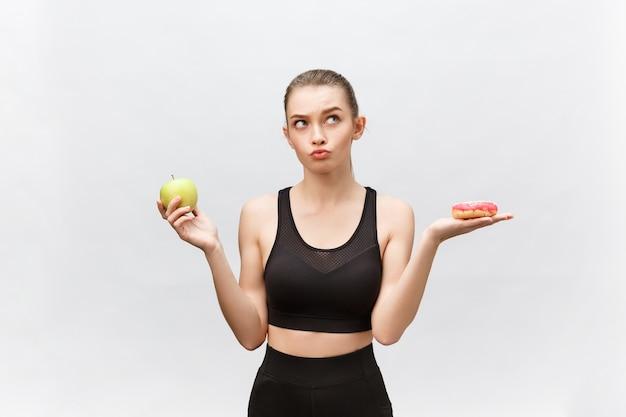 Jeune femme choisissant entre dessert et pomme régime alimentaire concept.