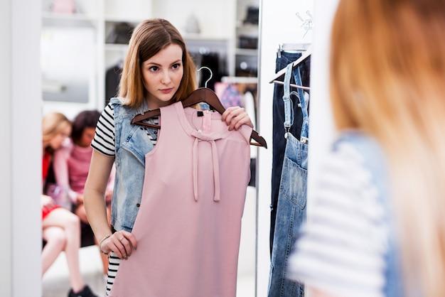 Jeune femme choisissant une nouvelle robe rose dans une boutique de mode