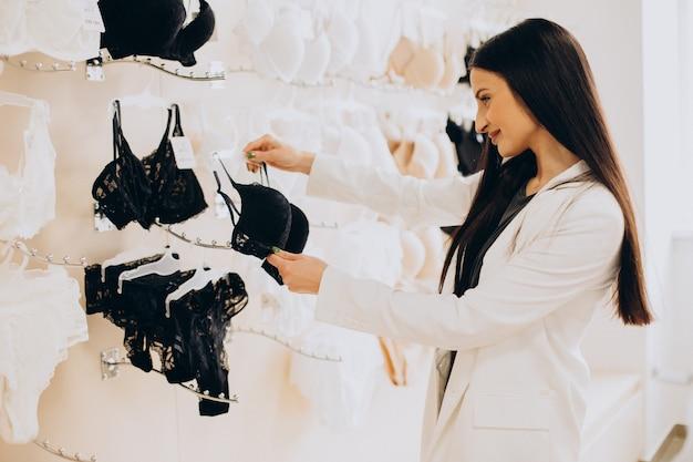 Jeune femme choisissant des sous-vêtements au centre commercial